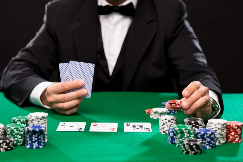 10813937-poker-player-with-cards-and-chips-at-casino